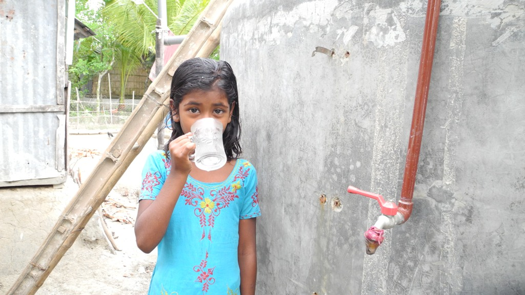A girl enjoys a drink of water from a solar based purification system supplied by CAFOD, Bangladesh.