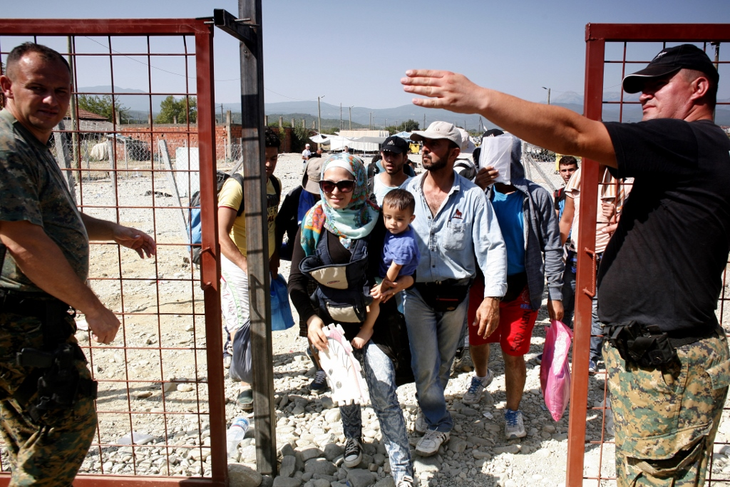 Refugees being directed at a barrier checkpoint, on their way to cross the Greek-Macedonian border.