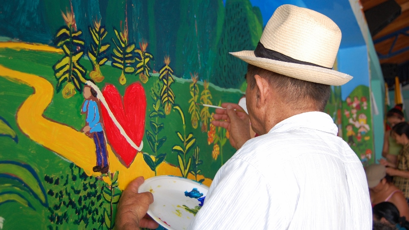 A man paints a memory mural in Colombia. In the painting a man is leaving his home with a heavy heart