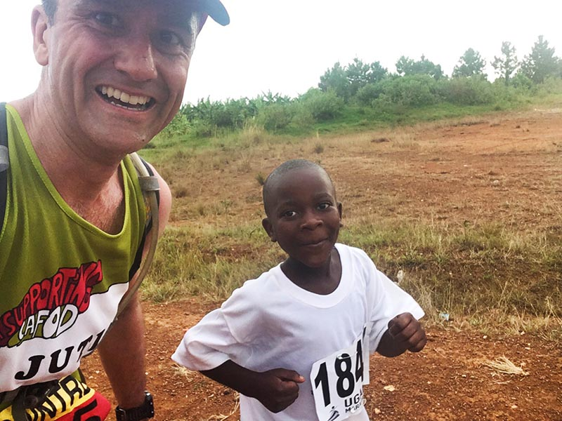 Justin runs with a local child during the Ugandan Marathon