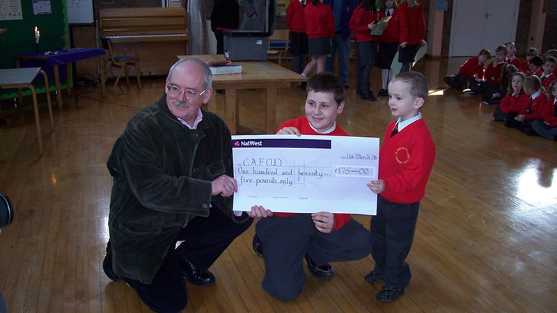 Volunteer Joe Andrew accepts a cheque from pupils at English Martyrs school in the Birmingham Diocese