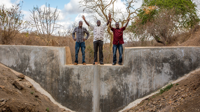 Project members celebrate on top of one of the sand dams