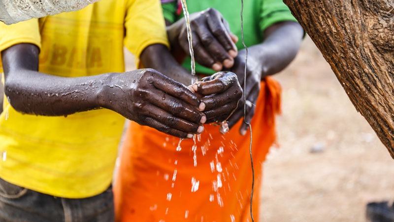 A young boy washes his hands in Musosya, Kenya