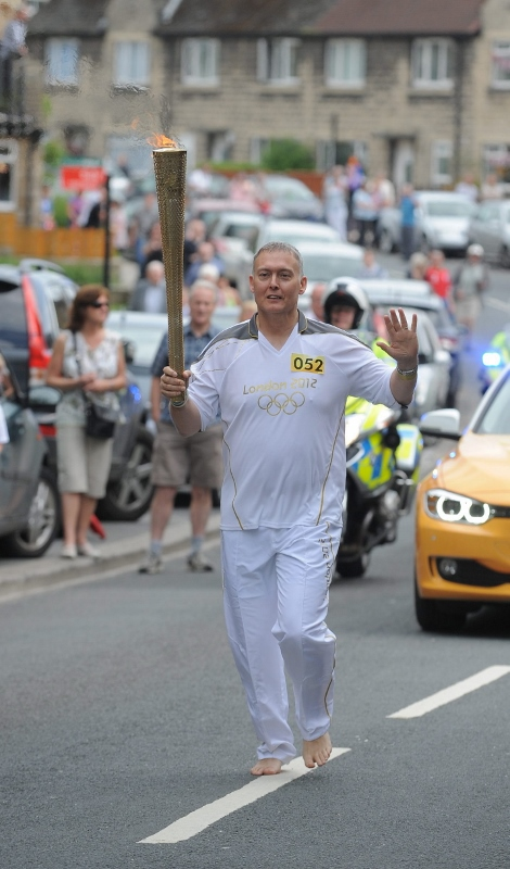 John runs barefoot with the Olympic torch. Photo credit: Craig Connor North News & Pictures Ltd