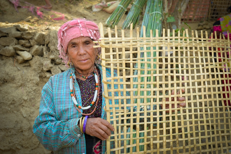 Jyotimaya, 60, uses bamboo she received from CAFOD's partners to earn a living by making and selling baskets and fencing