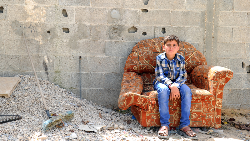 mohammed-sitting-on-a-damaged-chair-in-his-old-home-that-was-destroyed-in-the-2014-gaza-conflict