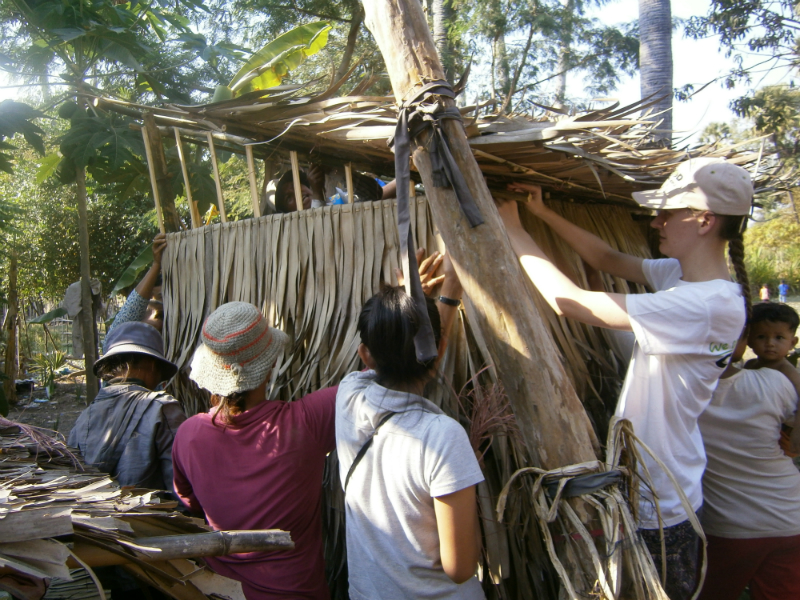 The villagers use Lizzie's height to their advantage as they construct the upper parts of the latrine walls.