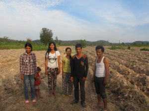 Suong (far left) and her family are Cassava farmers. Here they are standing in their Cassava field.