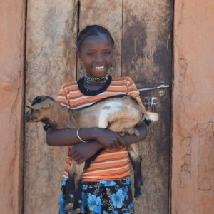 African girl holding the goat she received from CAFOD