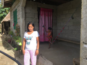 woman stood outside her new sturdier, typhoon resistant home..
