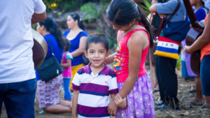 Brother and sister in El Salvador hold hands at a prayer service