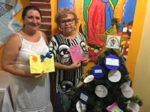 Jenilda and Zeza stand holding Christmas messages beside a Christmas tree in the Cultural Centre in Vila Prudente. There is a CAFOD bauble on the Christmas tree.