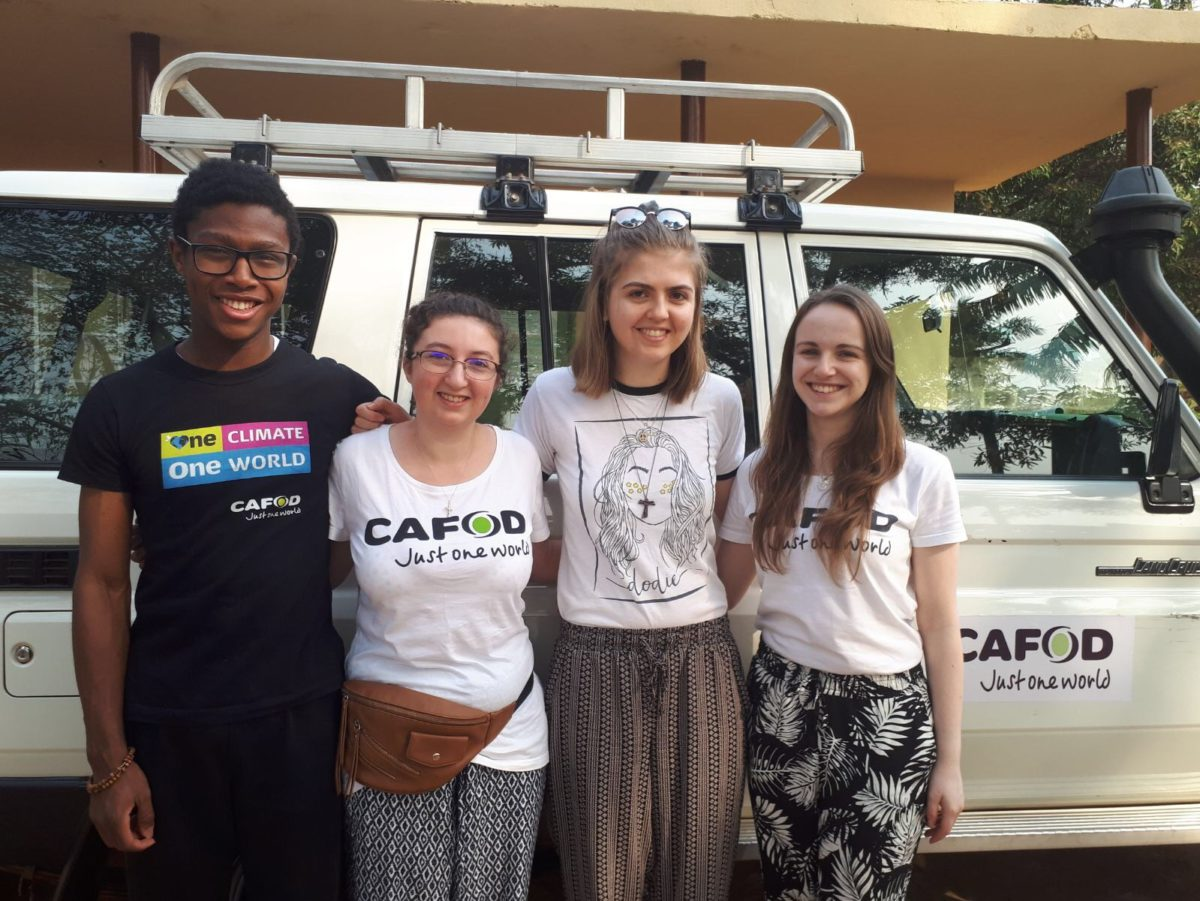 A group of CAFOD young gap year volunteers standing by a white 4x4 in Sierra Leone.