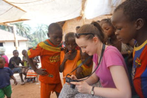 Hannah showing her photos to the children in Kambia