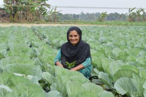 Razia Begum proudly displaying vegetables she has grown using vermi compost
