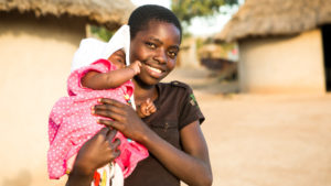 A 12-year-old girl holds her baby sister in Zimbabwe. Their mother, Marian has been supported with vegetable seeds, nutrition and farming training, and fenced off a community vegetable garden to keep it safe from livestock. Marian is now growing a range of nutritious vegetables, nuts and beans for her children