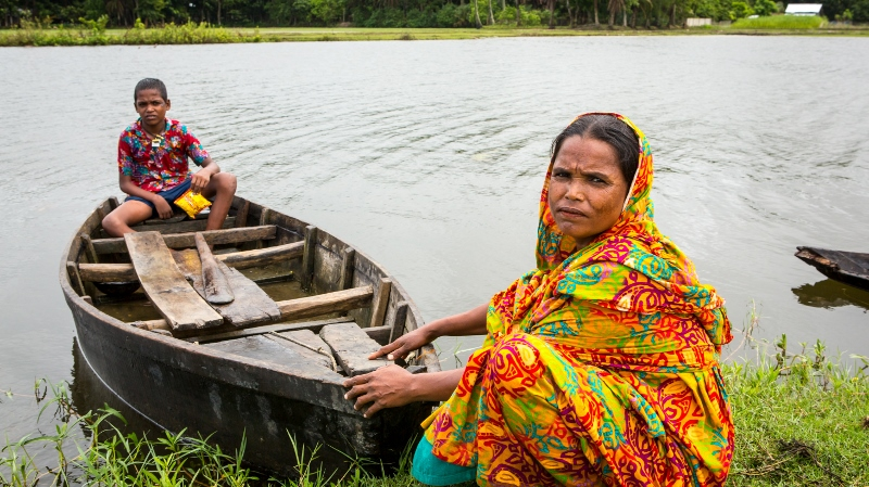 Mahinur crouches by the riverbank holding a small boat with her son Rabiul in,
