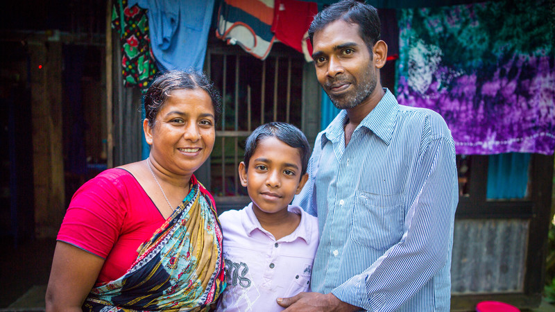 Eshita stands smiling with her son and husband