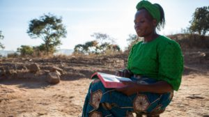 Beauty sits outside her home in Zambia reflecting on the Bible