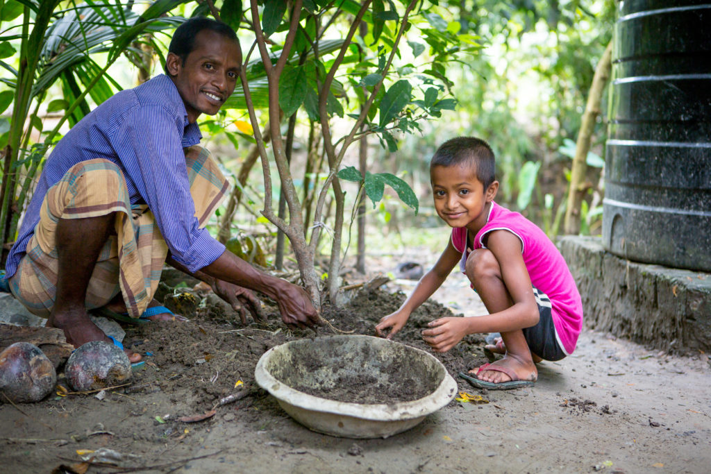 A man and a small boy smiling and digging in the mud in their garden in Bangladesh
