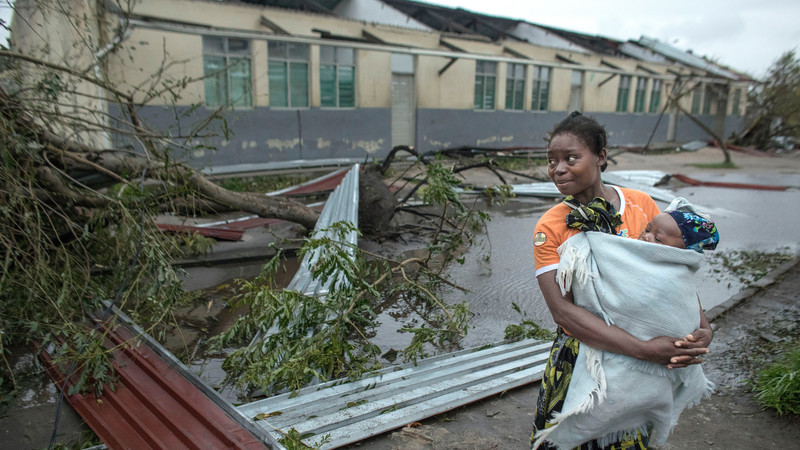 A woman holding her baby standing next to a building wwhose roof has been destroyed in Cyclone Idai in Mozambique. There are trees and sheets of corrugated metal on the floor at her feet