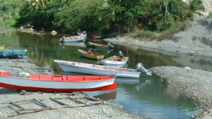 Small wooden fishing boats partially submerged in shallow water