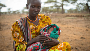 A Kenyan woman sits and holds her baby