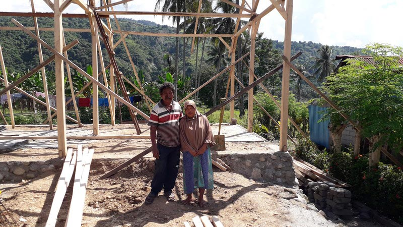 A family from Salua village stand in front of their new home