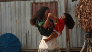 At a festival celebrating indigenous culture, Manaus, Brazil a girl dances with a young child