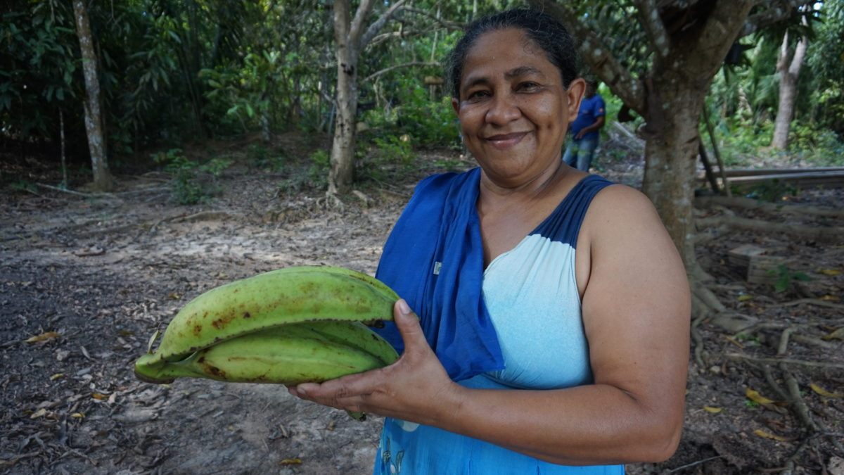 Dona Maria proudly holds her plantain grown in the Amazon rainforest without chemicals.
