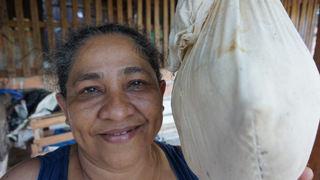 Dona Maria at home with her bag of tapioca flour.