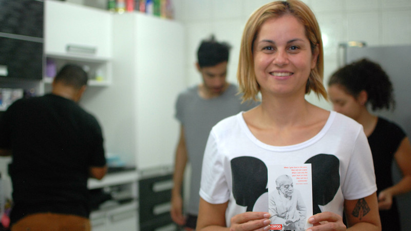 Ana Paula in Brazil holds a CAFOD postcard with a picture of Dom Helder Camara on it.