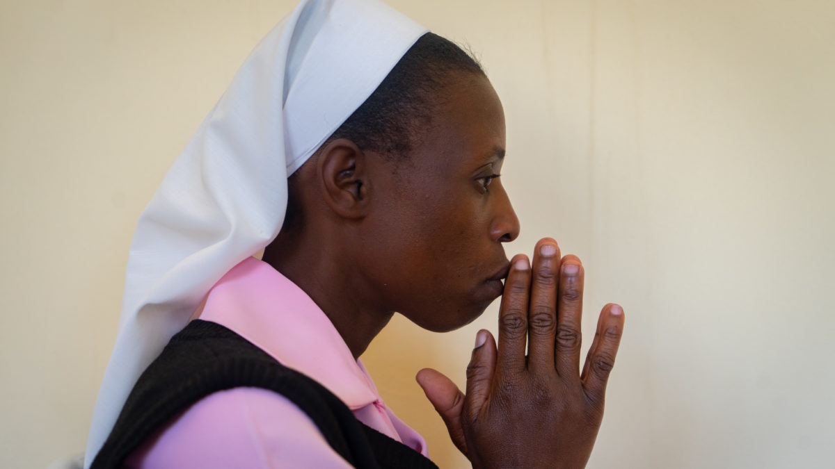 Sister Consilia stands with her hands clasped in prayer