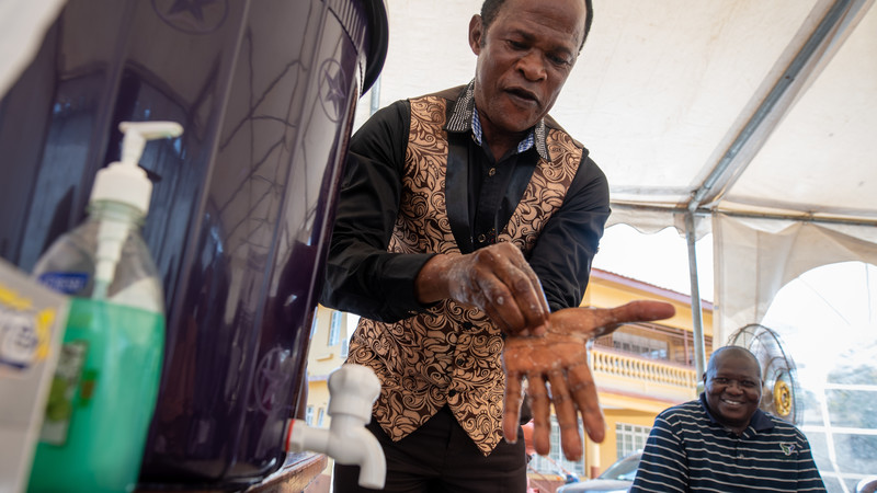 Reverend Augustine Samura-Banks washes his hands during a COVID-19 awareness training for religious leaders at CAFOD's office in Freetown
