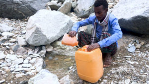 Abdlella scoops water from a puddle to fill a jerry can for his family