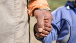 Close up of man and child holding hands in Bolivia